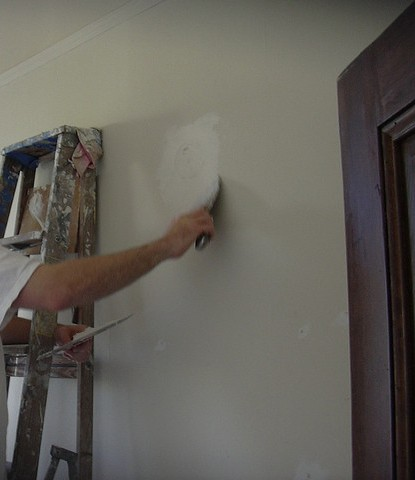 Man Preparing A Wall For Interior Painting