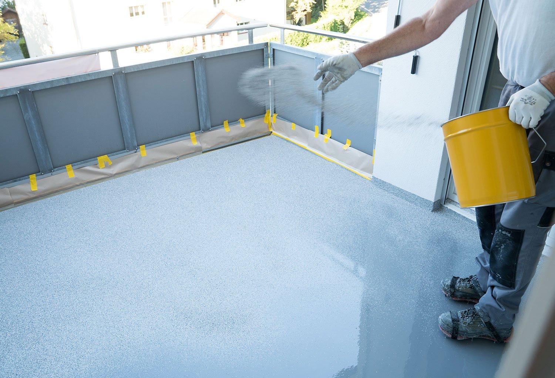 Worker applying epoxy floor coating