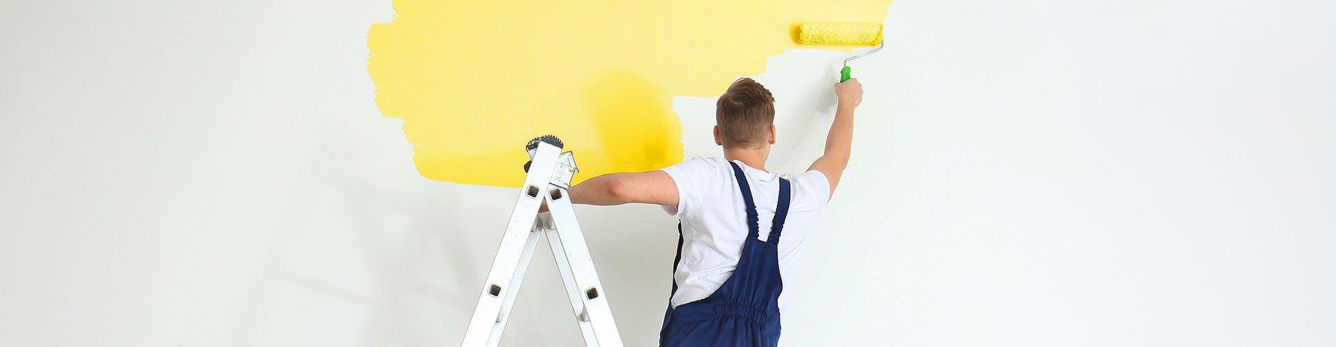 Painting contractor rolling wall of building